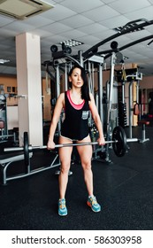 Beautiful fitness brunette woman lifting barbell. Sporty woman lifting weights. Fit girl exercising building muscles. Fitness and bodybuilding. front view.