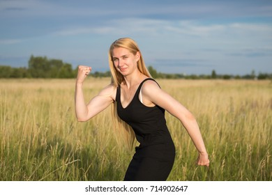 beautiful fitness girl blonde funny showing her muscles on outdoors