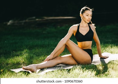 Beautiful fitness girl exercising in nature on sunny summer day.