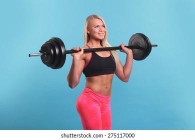 Beautiful fitness girl liftings weights. studio photo