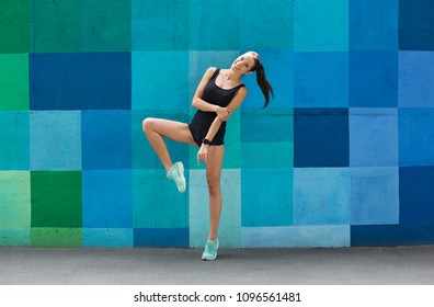 Beautiful fitness girl posing on blue wall background outdoors, copy space. Sporty woman with perfect body, healthy lifestyle and bodycare concept