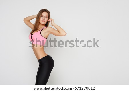 67fcdca556 Beautiful fitness girl posing on studio background. Portrait of confident  sporty woman with perfect body