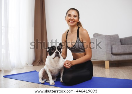 Beautiful fitness girl sitting on floor with dog
