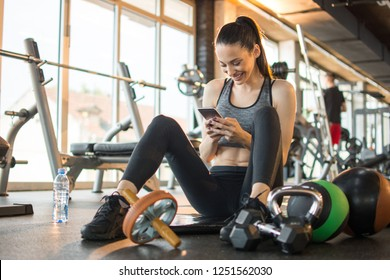 Beautiful fitness girl sitting and relaxing on exercise mat and using phone in the gym