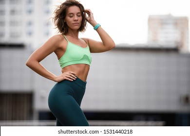 Beautiful fitness girl in sportswear resting after workout session standing on urban street. Concept of sport, wellness and health.