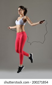beautiful fitness jumping the rope, studio shot