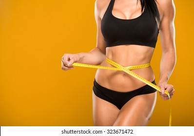 beautiful fitness model measures the waist on a yellow background