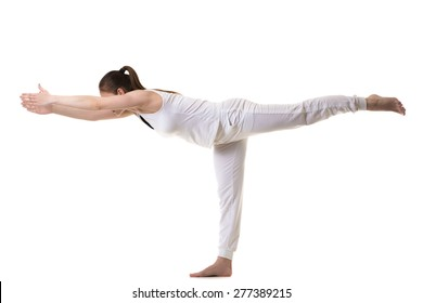 Beautiful fitness model practices yoga or pilates, doing exercise for legs and back, balancing in Warrior III posture, Virabhadrasana 3, side view, studio shot, isolated