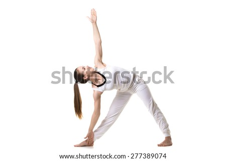 Beautiful fitness model practices yoga or pilates, standing in Triangle yoga pose, Trikonasana, stretching exercise, front view