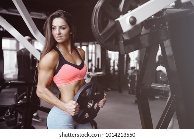 Beautiful fitness sexy athletic muscular young brunette Caucasian fitness girl working out training in the gym gaining weight pumping up abs muscles and poses bodybuilding health care concept