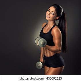 Beautiful fitness smiling woman with  lifting dumbbells . Sporty girl showing her well trained body .  Well-developed muscles by strength training .