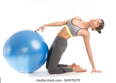 Beautiful fitness woman doing pilates exercises with fit ball. Isolated on white.