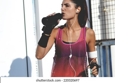 beautiful fitness woman drinking water, outdoor shot