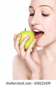Beautiful fitness woman eating healthy apple on white background