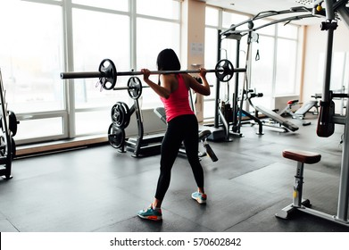 Beautiful fitness woman lifting barbell. Sporty woman lifting weights. Fit girl exercising building muscles. Fitness and bodybuilding. front view.