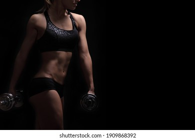 Beautiful fitness woman lifting dumbbells on a black background