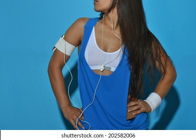 beautiful fitness woman posing against the blue background