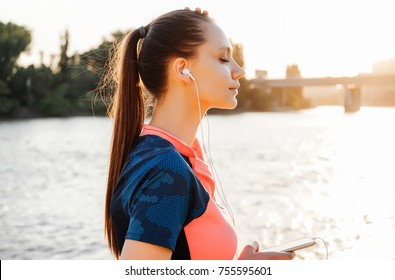 beautiful fitness woman in sportswear listening music on headphones by the river at sunset