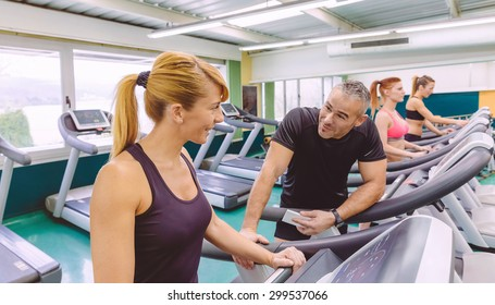 Beautiful fitness woman in a treadmill talking with handsome man on a fitness center