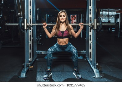 beautiful fitness young girls doing squats with the barbell in smith machine at the gym. Perfect fitness female figure