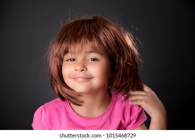 Beautiful five years girl with a wig smiling in black background. Studio shot