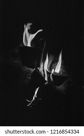 Beautiful flames of fire in night on film. Minimalist evening campfire in darkness. Atmospheric scanned analog photography with grain and scratch. Glowing embers in air. Lomography of bonfire.