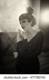 Beautiful Flapper girl. Old photo in a retro style. Smoky eyes and hair cold wave.