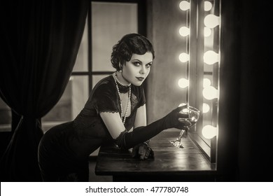 Beautiful Flapper girl with wineglass. Old photo in a retro style. Smokey eyes, hairstyle cold wave.