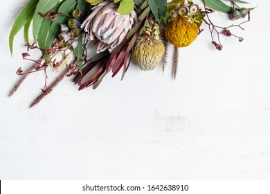 Beautiful flat lay floral arrangement of mostly Australian native flowers, including a pink protea, yellow banksia, red kangaroo paw, eucalyptus leaves and gum nuts on a white background.