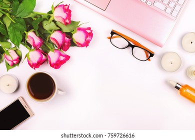 Beautiful flat lay with laptop, flowers, cosmetics, glasses, candles and other accessories, concept of a woman's workplace, white background