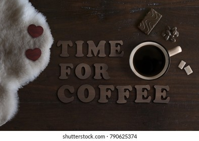 beautiful flat lay of mug with coffee, sheepskin, chocolate and text time for coffee, on rustic wooden background