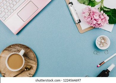 Beautiful flatlay arrangement of woman's work desk with pink laptop, cardboard, hortensia, glasses and other accessories. Feminine business mockup