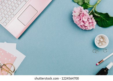 Beautiful flatlay arrangement of woman's work desk with pink laptop, hortensia and other accessories. Feminine business mockup