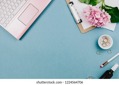 Beautiful flatlay arrangement of woman's work desk with pink laptop, cardboard, hortensia and other accessories. Feminine business mockup