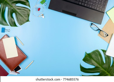 Beautiful flatlay with a laptop, glasses, philodendron leaves and other business accessories. Concept of a home office. Flat lay. Blue background.
