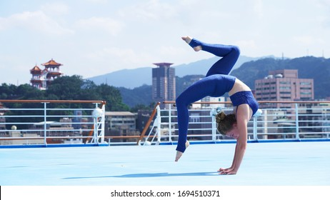 Beautiful flexible girl professional circus acrobat performer handstand, gymnastic bridge, backbend position, graceful woman on cruise liner, sports model on blue background, ship, Asian temple, city