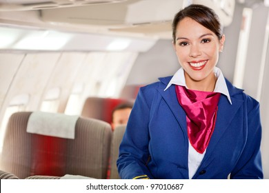 Beautiful flight attendant in an airplane cabin smiling