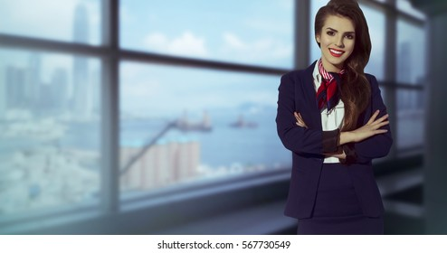 Beautiful flight attendant with scarf and dress suit. Smiling on airport.Happy stewardess on airport with crossed arms. Elegant female beside windows.