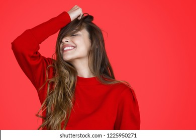 Beautiful flirty woman playing with hair and closing eyes in daydreams on red background