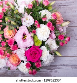 beautiful floral arrangement in the box, pink and yellow rose, pink eustoma, green and pink chrysanthemum, white carnation, dahlia on wooden background, top view, with space for text