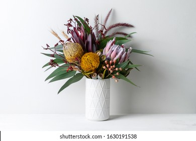 Beautiful floral arrangement of mostly Australian native flowers, including protea, banksia, kangaroo paw, eucalyptus leaves and gum nuts, in a white vase on a white table with a white background.
