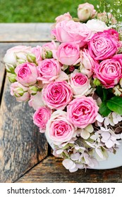 Beautiful floral arrangement with pink roses, hortensia and gypsophila paniculata. Flowers in simple vase.