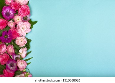 Beautiful floral background, texture, wallpaper. Flat-lay of pink flowers on blue background, top view, copy space greeting card or wedding invitation