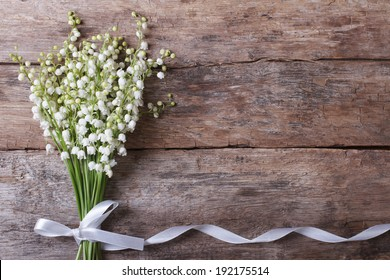 Beautiful floral frame with lilies of the valley flowers on old wooden table. horizontal