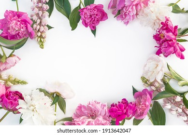 Beautiful floral frame of pruple, pink and white peonies and lupines on white background. Space for text