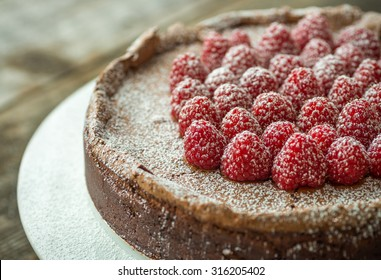 Beautiful flourless chocolate torte with raspberries and powdered sugar
