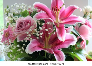 Beautiful flower arrangement of pink large-headed roses, pink germinis, pink Oriental lily, white spray chrysanthemum and pink lisianthus
