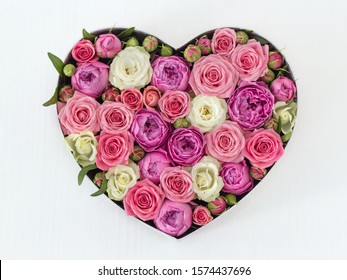 beautiful flower arrangement in the shape of a heart on a white wooden table close-up with a blurred background. white Bush rose, pink shrub rose, peony rose. as a gift, as a background, as a postcard