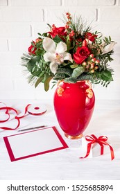 Beautiful flower arrangement of white orchid, red roses, natural spruce branches in red vase next to empty greeting card for text, gift box on white background-preparation for congratulations concept.