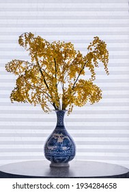 A beautiful flower arrangement of yellow sprigs of mimosa in a traditional Chinese porcelain vase stands on a round table against the background of a curtained window
